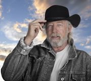 Handsome mature man wearing a black hat. Handsome mature man wearing a gray jeans jacket and black felt cowboy hat with blue eyes with sunset in background royalty free stock photo