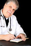 Handsome mature medical doctor writing a script Stock Photo