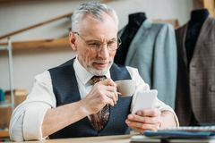 Handsome mature tailor drinking coffee and using smartphone. At sewing workshop stock photography