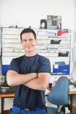 Handsome mechanic at auto repair shop. Portrait of a handsome smiling mechanic with arms crossed Stock Images