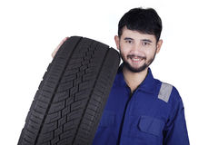 Handsome mechanic carrying a tire in studio. Portrait of a young Arabic mechanic smiling at the camera while carrying a tire in the studio, isolated on white Royalty Free Stock Images