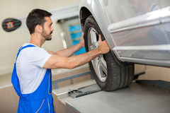 Handsome mechanic changing a tire Royalty Free Stock Image