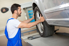Handsome mechanic changing a tire Royalty Free Stock Photo