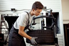 A handsome mechanic is helping his workmates at a car service stock photos