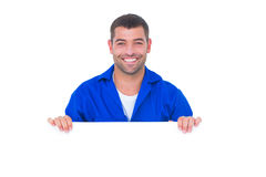 Handsome mechanic holding blank placard Stock Images