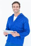 Handsome mechanic holding digital tablet. Portrait of handsome mechanic holding digital tablet over white background Royalty Free Stock Photography