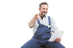 Handsome mechanic holding tablet and pointing you. Handsome mechanic holding digital tablet and pointing finger at you isolated on white background with Royalty Free Stock Photography
