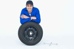 Handsome mechanic leaning on tire Stock Image