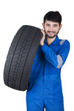 Handsome mechanic lifting tire in studio Stock Image