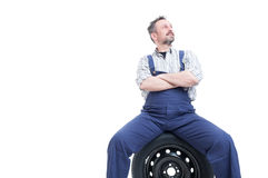Handsome mechanic man standing with folded arms. Handsome mechanic man standing confident with folded arms on tire looking up isolated on white with copy space Royalty Free Stock Photo