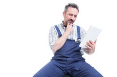 Handsome mechanic reading something on digital tablet. As technology and modern lifestyle concept isolated on white background with copyspace Stock Image