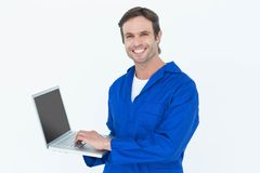 Handsome mechanic using laptop over white background Stock Photography