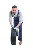 Handsome mechanic in workshop changing car wheel Stock Image