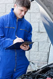 Handsome mechanic writing on a clipboard Stock Image