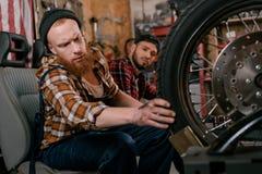 handsome mechanics examining wheel of motorcycle stock photos