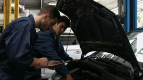 Handsome mechanics overhauling a car. In the garage stock video footage
