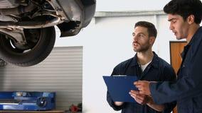 Handsome mechanics overhauling a car stock video footage