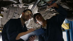 Handsome mechanics overhauling a car. In the garage stock footage
