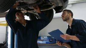 Handsome mechanics overhauling a car. In the garage stock video