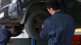 Handsome mechanics repairing a car stock video
