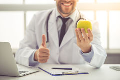 Handsome medical doctor. Cropped image of handsome medical doctor in white coat holding an apple, showing Ok sign and smiling while working in his office Royalty Free Stock Photography