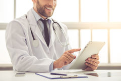 Handsome medical doctor. Cropped image of handsome medical doctor in white coat using a digital tablet and smiling while working in his office Stock Images