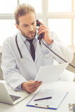 Handsome medical doctor. In white coat is talking on the phone and examining documents while working in his office Stock Photos