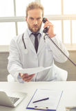 Handsome medical doctor. In white coat is talking on the phone, holding documents and looking at camera while working in his office Royalty Free Stock Photography