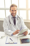 Handsome medical doctor. In white coat is using a digital tablet, looking at camera and smiling while working in his office Royalty Free Stock Photos