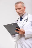 Handsome medical specialist working alone. Portrait of an old practitioner standing and holding the tablet Royalty Free Stock Image