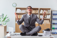 The handsome meditating on the office desk. Handsome meditating on the office desk Stock Image