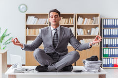 The handsome meditating on the office desk Royalty Free Stock Photography