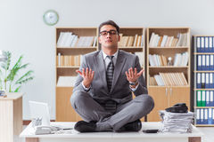 The handsome meditating on the office desk Stock Images