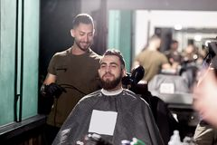 Handsome man with beard sits at a barber shop in front the mirror. Barber makes a hair trim. stock photos