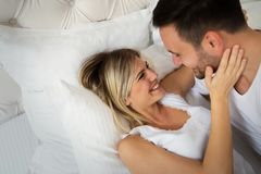 Handsome man and beautiful woman kissing each other. Handsome men and beautiful women kissing each other on bed Stock Photos
