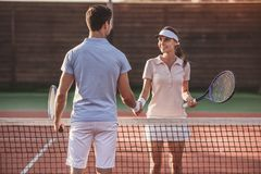 Couple playing tennis. Handsome men and beautiful women are shaking their hands while playing tennis on tennis court outdoors Royalty Free Stock Images