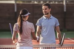 Couple playing tennis. Handsome men and beautiful women are shaking their hands while playing tennis on tennis court outdoors Royalty Free Stock Photography