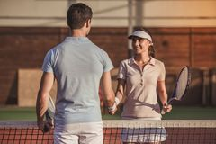 Couple playing tennis. Handsome men and beautiful women are shaking their hands while playing tennis on tennis court outdoors Stock Photos