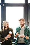 Handsome men colleagues in office talking with each other Stock Images