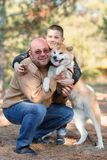 Happy little boy and man walking with dog in the park. Animal concept. Handsome men and cute little boy having fun with doggie in the park outdoors. Happy Stock Image