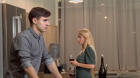 Handsome man drinking wine after having a fight with his girlfriend at home stock photography