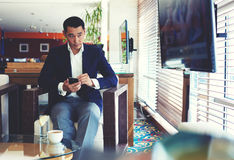 Handsome men entrepreneur with serious face looking aside while relaxing in cafe Stock Images