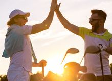 Men playing golf. Handsome men are giving high five and smiling when meeting on a golf course Stock Photos