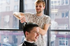 Handsome man at the hairdresser getting a new haircut stock photos