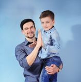 Handsome man and his son. Handsome men and his son on color background Stock Photography