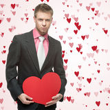 Handsome men hold big red heart. Handsome man hold big red heart over small flying hearts on background Stock Photos