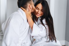 Handsome man kissing beautiful woman on cheek while stock photo