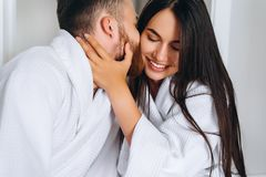 Handsome man kissing beautiful woman on cheek while royalty free stock image