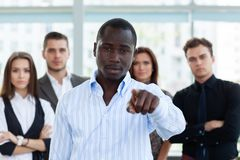Handsome man pointing his finger at you on the background of business people. stock images