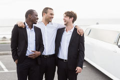 Handsome men posing next to a limousine Royalty Free Stock Photos